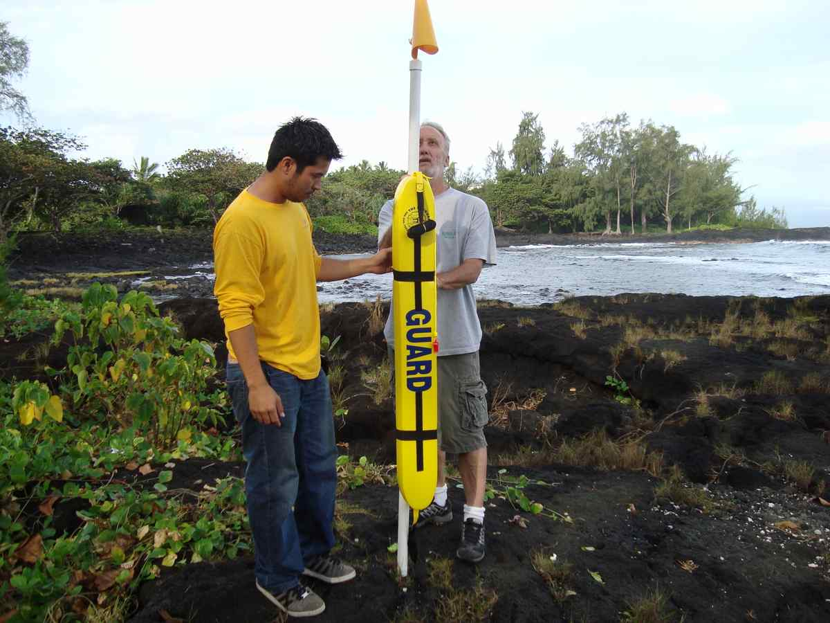 Rotary Club of South Hilo members Dayle Tejada, left, and Gene Hennen finish installing the first donated rescue tube Thursday at Lehia Beach Park in Hilo. Courtesy photo.