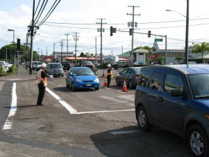 Special-duty police officers direct traffic at the busy intersection of Kilauea Avenue and Pauahi Street Friday afternoon. Motorists are being advised to avoid the area this weekend as the repaving work will continue Saturday and Sunday. Photo by Dave Smith.