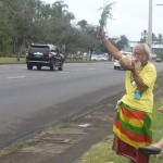 Sovereignty activist Abel Lui waving at passing motorists on Kamehameha Avenue this afternoon. Photo by Dave Smith.