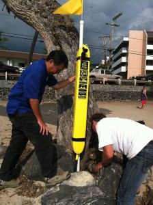 Kevin Sakai of the county Department of Parks and Recreation, left, and Mike Varney scout a location for a rescue tube at Magic Sands beach in Kona. Foundation photo.