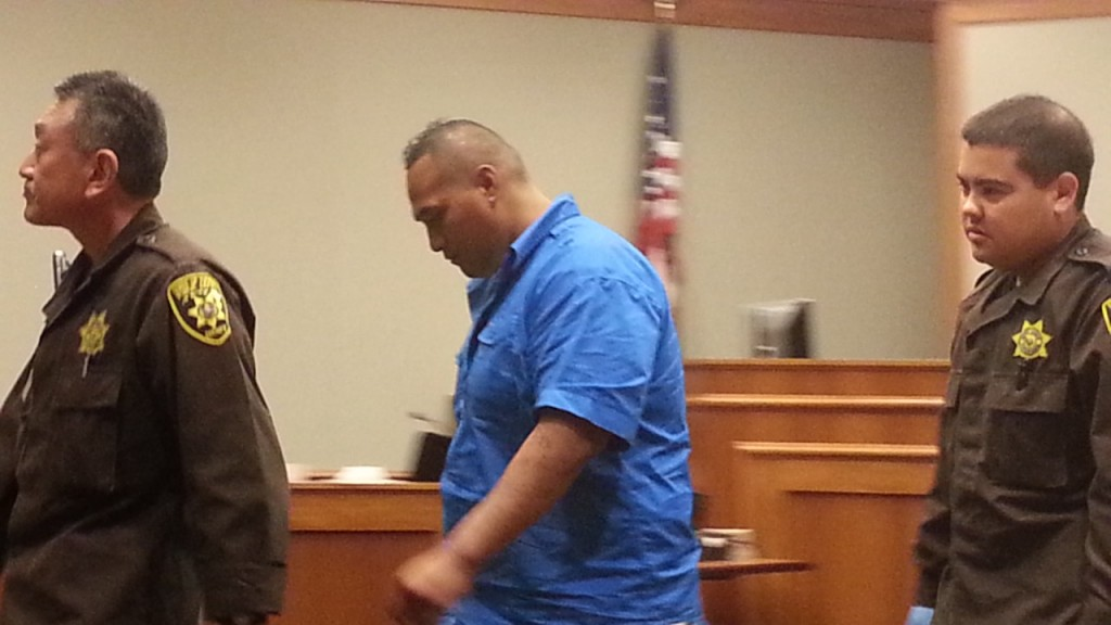Siuika Aholelei being taken into custody following today's hearing. Photo by Dave Smith.