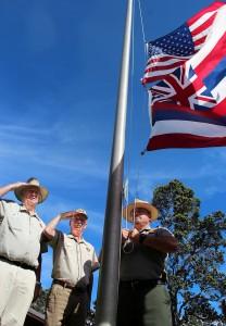 HVNP-Vets-Salute Hawaii Volcanoes National Park volunteers George Jensen (left) and Paul Field salute as Park Ranger Keoni Kaholoa'a raises the flags outside Kīlauea Visitor Center.