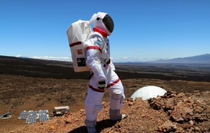 """The HI-SEAS simulation includes participants wearing """"spacesuits"""" when outside their living area. The solar array that provides power can be seen at left. Photo by Angelo Vermeulen."""