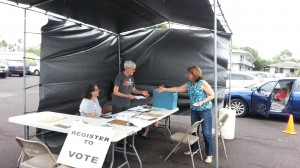 Election worker Sue Irvine, center, accepts a voter registration form today at the Hilo drive-thru location. Photo by Dave Smith.