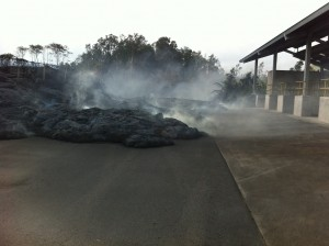This photo, taken Nov. 13, shows the flow entering the Pahoa transfer station. There are no active toes of lava in the image, but the lava is still hot enough to burn the asphalt beneath, creating visible white smoke. HVO photo.