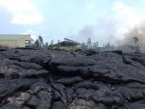 This Nov. 11 photo shows  the breakout near the transfer station and how it has inflated up to the level of the Pāhoa transfer station fence. A glowing crack provides evidence of the flow's molten interior. HVO photo.