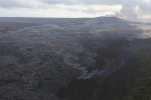 A breakout from the lava tube has also been active on the upper part of the flow field near Puʻu ʻŌʻō since December 5. The smoke is from a narrow finger of lava burning lichen on an older Puʻu ʻŌʻō lava flow. Puʻu ʻŌʻō is at upper right. The view is to the south-southwest. HVO photo.