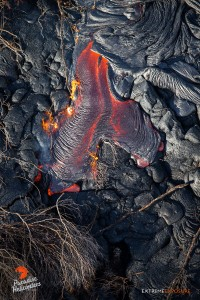 In this photo, taken Feb. 24 at 8 a.m., a leathery toe of lava ignites the dried branches of toppled trees on the flow field. Photo credit: Extreme Exposure Media/Paradise Helicopters.