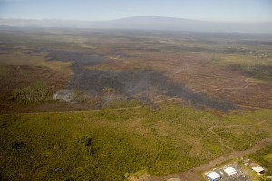 In this photo, taken on Feb. 19, another view of the leading portion of the June 27th flow, looking upslope. Pahoa Marketplace is in the lower right corner of the photograph. Mauna Loa can be seen near the top of the photograph. USGS HVO photo.
