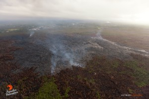 In this photo taken on Feb. 9, a breakout along the southern perimeter looks to have advanced within the flow's boundaries (lighter toned lava on the right), and now begins to enter the brush. Photo credit: Extreme Exposure Media/Paradise Helicopters.