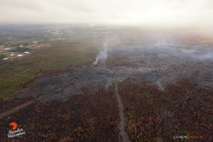 Activity resumes about 100 yards upslope of the stalled flow front, as lava from a fresh breakout was pouring into a depression or crack in the ground, indicated by the rising smoke near the center of the photo, taken on Feb. 9. Photo credit: Extreme Exposure Media/Paradise Helicopters.
