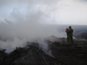 After establishing an appropriate location to resume VLF measurements over the June 27 lava tube to estimate the cross-sectional area of lava within the tube, HVO geologists on March 17 make the measurements, sometimes requiring walking through volcanic gases. USGS HVO photo.