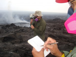 The VLF radio wave, transmitted from the Lualualei Naval Base on Oʻahu, is received by the handheld device. The numbers are read and recorded. These data will allow the estimation of the cross-sectional area of lava within the tube. This photo, taken March 17, shows scientists going through the process. USGS HVO photo.