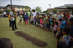 Children and residents of The Homes at Ulu Wini gather around Kahu Brian Broshard, who led the playground blessing and groundbreaking ceremony. HOPE Services Hawai'i photo.