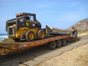 DLNR Land maintenance crew hauls the skiff from Alan Davis beach onto a trailer on April 24. Photo by DLNR.