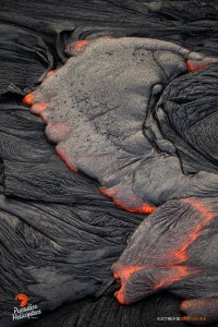 April 16, 2015. The cooled surface of a pahoehoe flow breaks loose, releasing molten lava in the middle of the flow field. Photo credit: Extreme Exposure Media/Paradise Helicopters.