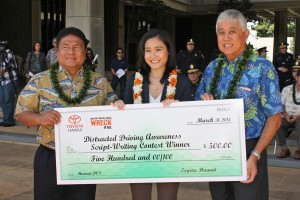 Contest winner Haruna Yamanaka (center) was presented with a $500 check by Glenn Inouye of Servco Pacific (right) and HDOT Deputy Director Jade Butay (left) during Tuesday's event. Her winning concept and script will be professionally produced and broadcast on television and in movie theaters statewide over the summer. HDOT photo.