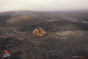 April 16, 2015. Pu'u Kahauale'a sits in the foreground, while Pu'u 'O'o is hidden by the low cloud cover. Visible on its northeastern flank is the perched pond that was a product of the June 27 breakout. Photo credit: Extreme Exposure Media/Paradise Helicopters.