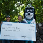 Just before the UnitedHealthcare IRONKIDS Keiki Dip-n-Dash, UnitedHealthcare mascot Dr. Health E. Hound helps present a $3,000 check to Kama'aina Kids to support its youth health programs. (Left to right: Mark Nishiyama, Vice President of Kama'aina Kids; Dr. Ron Fujimoto, Chief Medical Officer for UnitedHealthcare's Community Plan for Hawaii; Dr. Health E. Hound, UnitedHealthcare). Photo credit: UnitedHealthcare.