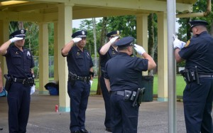 Officer salute as the United States and Hawai'i flags are raised at Lincoln Park in Hilo. HPD photo.