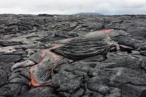 Lava, like this typical pāhoehoe flow on Nov. 12, 2015, continues to breakout northeast of Pu'u 'Ō'ō (in background) on Kīlauea Volcano. Current activity is within about 6 km (4 mi) of the vent and poses no immediate threat to Puna communities. USGS photo.