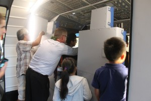 Rob Kelso, PISCES Executive Director, with several students Thursday as they investigate the new space shuttle flight simulator at Kea'au High School. PISCES courtesy photo.