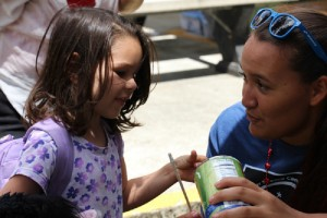 Malia Kealoha of Maui, a camper at last summer's Science Camp, shares a chemistry experiment with a young attendee at the Volcano Village 4th of July Festival. Courtesy photo.