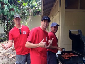 Past Hawai'i Island Portuguese Chamber of Commerce Presidents Charles Ensey, Joe Marsh, and Billy Andrade grill Portuguese sausage hot dogs at Carvalho Park during last year's event. Courtesy photo: Larkin Correia.