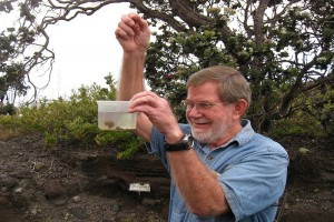 During a 2015 field trip with Franklin and Marshall College students, Don Swanson, a geologist at the USGS Hawaiian Volcano Observatory, demonstrates that reticulite (frothy basalt, less dense than pumice, explosively erupted in lava fountains) sinks, rather than floats, in water due to its high permeability. Swanson is the recipient of two prestigious awards honoring his career as a research volcanologist and science communicator. USGS/HVO photo.