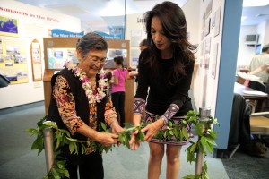 Millie Uchima (left) and Marlene Murray (right), Executive Director for the Pacific Tsunami Museum untie a maile lei during a traditional blessing ceremony to unveil the brand new Science Room. Courtesy photo.