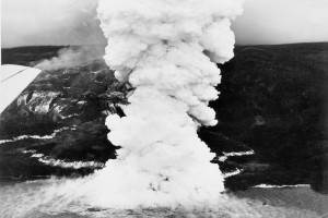 During the Mauna Loa 1950 eruption, three large, fast-moving lava flows advanced down the west flank of the volcano, each crossing the main highway before reaching the ocean. The Ka'apuna flow, shown here, traveled from the Southwest Rift Zone vent (7,800 ft elevation) to the coast in just 17 hours, creating a huge steam plume as lava flowed into the sea. The glowing edges and fast-moving channels of the 10- to 25-ft thick 'a'ā flow appear white in this June 2, 1950, aerial image. Photo courtesy of Air National Guard, 199th Fighter Squadron.