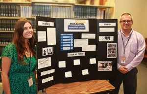 """Supreme Court Law Library staff members Chelsea DeMott and Jason Weekley are pictured above with the Library's """"Law Day 2016: Miranda More Than Words"""" display. Hawai'i State Judiciary courtesy photo."""