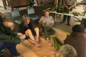 Ranger Dean shows visitors how to make tī leaf lei at Kīlauea Visitor Center. NPS Photo/David Boyle