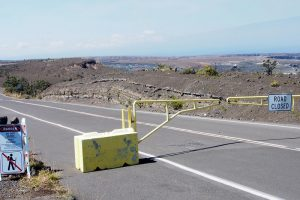Layers of explosive deposits erupted from Kīlauea Volcano in 17th and 18th centuries are visible in a road cut just beyond the gate at Keanakākoʻi Crater. This section of Crater Rim Drive has been closed since 2008, when the still-erupting vent within Halemaʻumaʻu Crater (middle, far right) first opened. USGS photo.