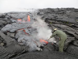 Amidst steam created by rain falling on the hot lava, another HVO geologist uses a rock hammer to collect a sample of the active flow, Wednesday. USGS/HVO photo.