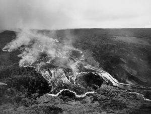This rapidly moving ʻaʻā lava flow was one of several that advanced down the west flank of Mauna Loa during the volcano's 1950 eruption. The massive flow, tens of meters (yards) high, traveled from the Southwest Rift Zone vent to the ocean, a distance of about 18 km (11 miles) in around 18 hours. Two earlier flows from this eruption reached the ocean in as little as three hours. All three flows crossed Highway 11 as they advanced to the sea. In this black-and-white aerial photo, incandescently hot areas on the flow appear white. Photo credit: Air National Guard, 199th Fighter Squadron.