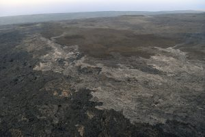 The new lava flow erupting from a vent on the eastern flank of Pu'u 'Ō'ō on Kīlauea Volcano's East Rift Zone appears silvery compared to older lavas over which it is flowing. The leading edge of the flow (visible fume in the upper left quadrant of photo) was about a mile from Pulama pali (fault scarp) on June 16, 2016. The coastal plain and ocean can be seen beyond the pali at the top of the photo. An HVO webcam (R3cam) provides imagery of this flow. USGS photo.