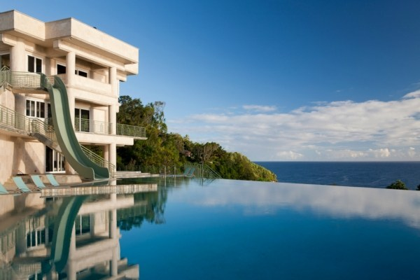 An olympic infinity pool dominates the front of the mansion.