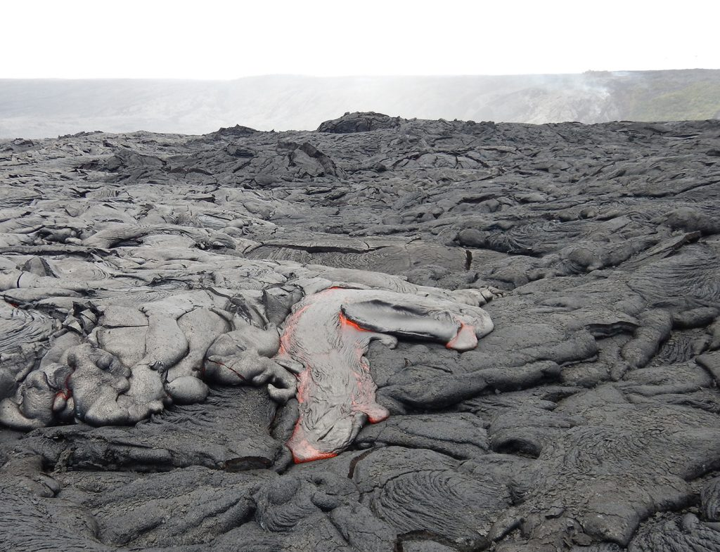 The active lava flow continues to creep across the coastal plain on Kīlauea's south flank. Breakouts of pāhoehoe (foreground) are fed by lava traveling through lava tubes from the Pu'u 'Ō'ō vent and down Pulama pali (top background). USGS photo.