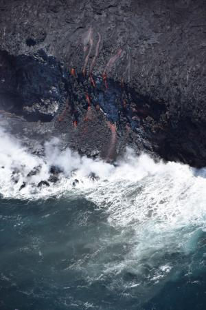 A close-up view of the ocean entry with multiple small fingers of lava spilling over the cliff. USGS photo.
