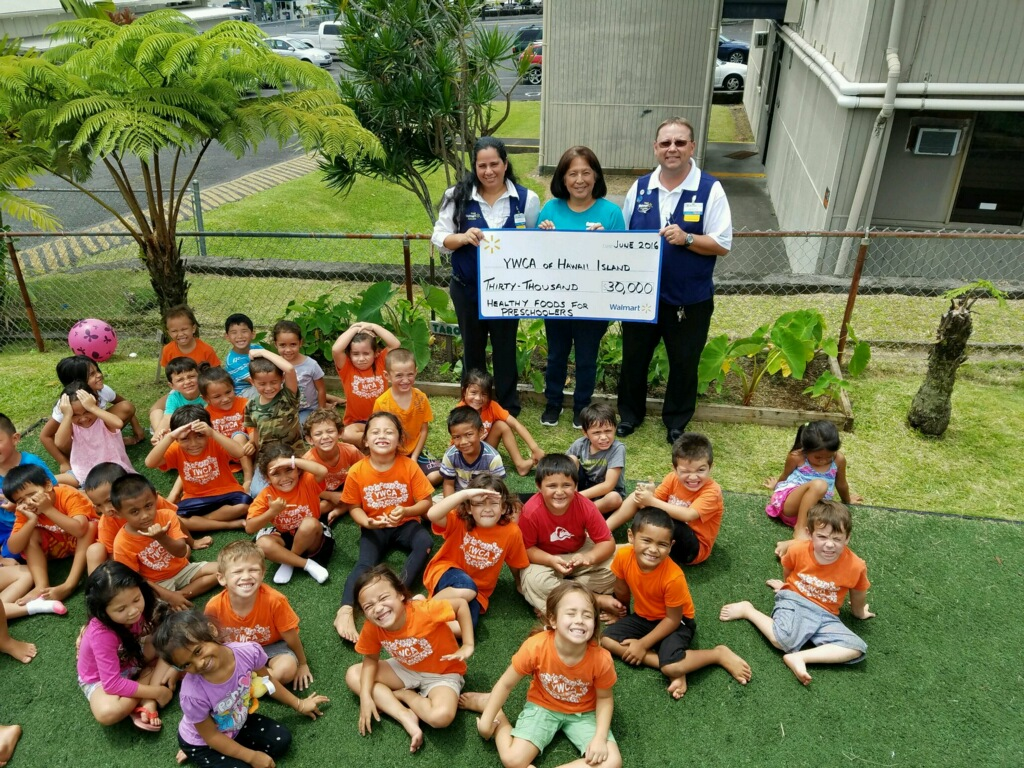 (Standing in the rear holding the check, left to right) Hilo Walmart Co-manager Sharyn Richardson, YWCA of Hawaii Island Preschool Director Lissa Van Kralingen, and Hilo Walmart store Manager Jerod Strong. Courtesy photo.