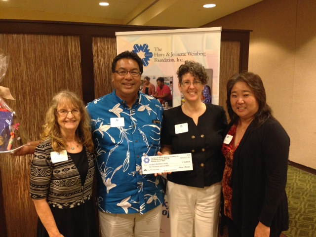 On behalf of Kuʻikahi Mediation Center, Executive Director Julie Mitchell (center) received $10,000 from Kathie Yamashiro (right) representing The Harry & Jeanette Weinberg Foundation, Inc. Courtesy photo.