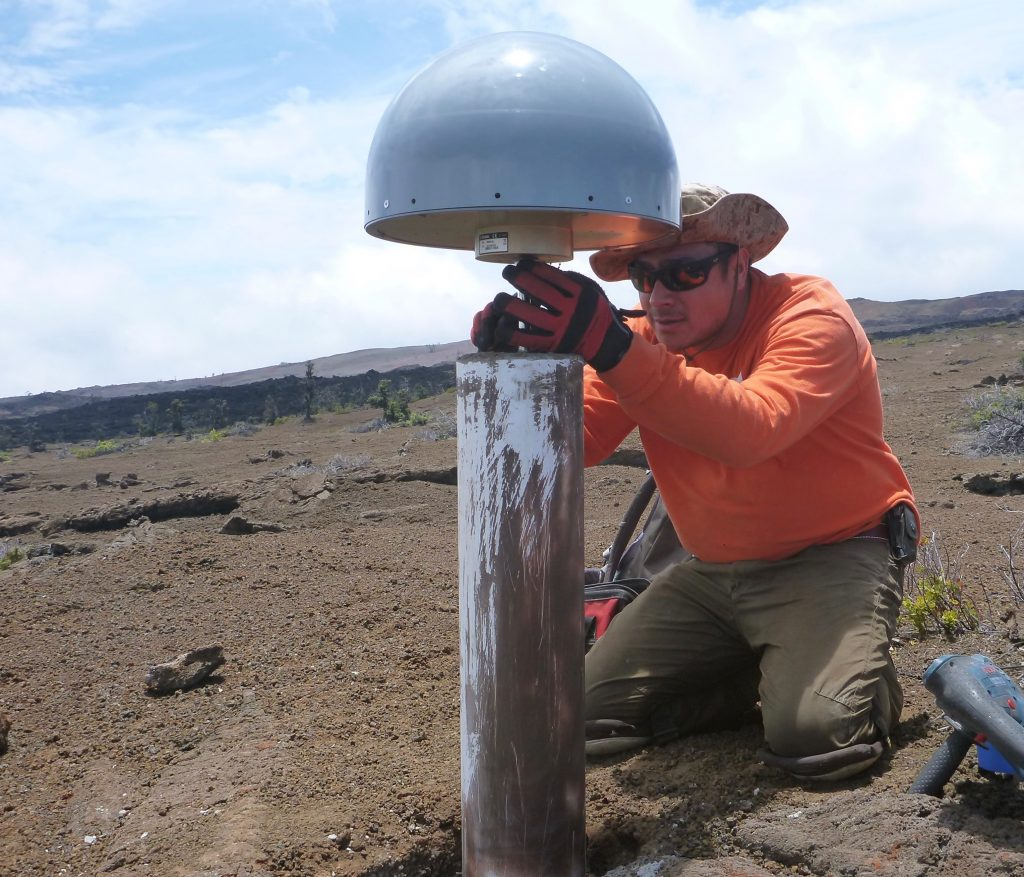 A USGS Hawaiian Volcano Observatory scientist puts the finishing touches on a new permanent GPS station on the slopes on Mauna Loa. The GPS antenna, protected from the elements by the grey radome, is solidly attached to the ground via a cement-reinforced steel rod. GPS is a critical tool for tracking ground motion on Hawaiian volcanoes. USGS photo.