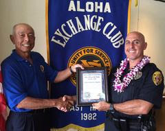 "Aloha Exchange Boardmember Joey Estrella presents an ""Officer of the Month"" award to Officer Roberto Segobia. HPD photo."