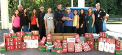 HPD Chief Harry Kubojiri presents 136 shoeboxes full of Christmas presents donated by police department personnel to Nell Quay, Operation Christmas Child area coordinator of East Hawai'i. To the chief's left is Steve Meek, the island's collections coordinator for the charity project.