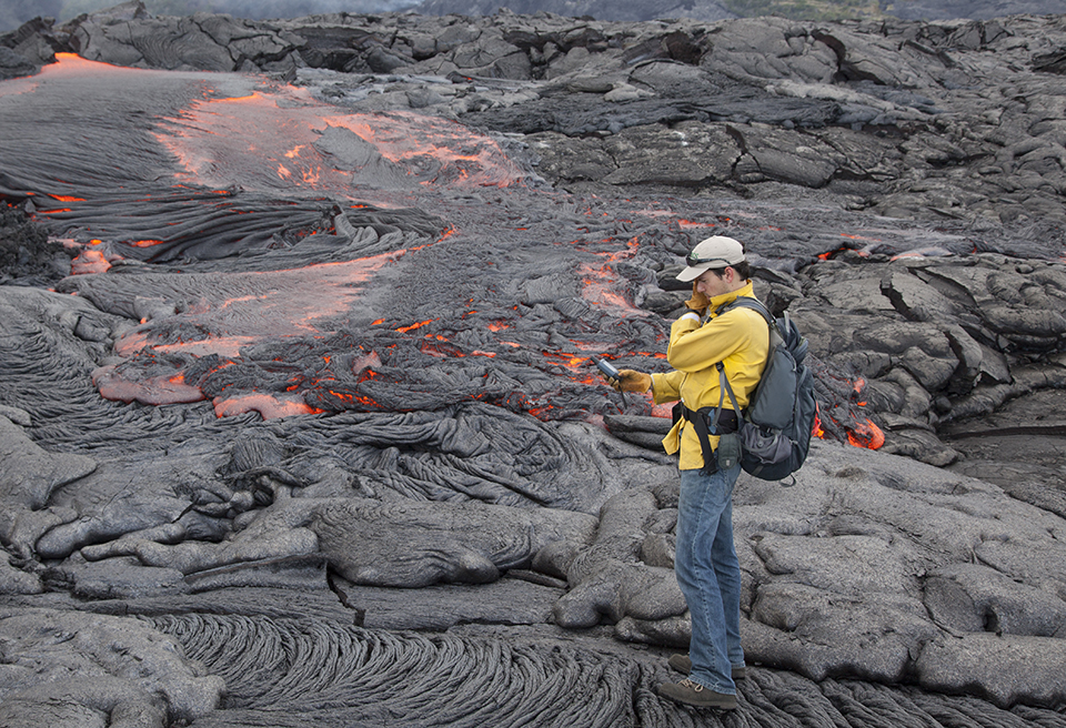 Hawaiian Volcano Observatory geologist mapping a lava flow in 2012. USGS photo.